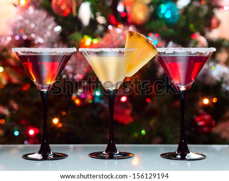 Three glasses with cocktails  against a Christmas fur-tree - stock photo