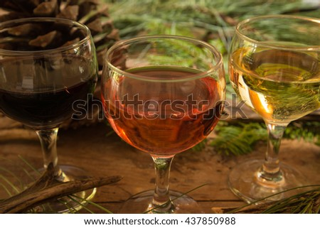 Three glasses with red, pink and white wine, deer antlers, pine cone, branch of pine on a wooden background