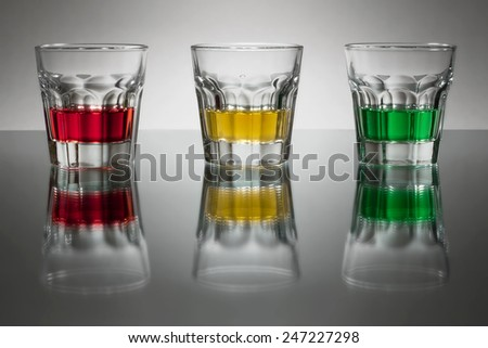 Three glasses with traffic light colored alcohol  - stock photo