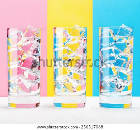 Three glasses with water and with pieces of ice on a colorful background. Thirst-quenching drink at summer for a party and relaxing. Pink, yellow and blue colors. Vintage style. - stock photo