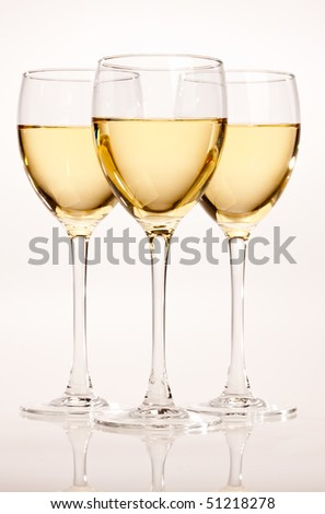 three glasses with white wine over light bsckground