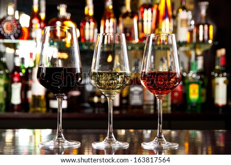 Three glassses of wine on the counter - stock photo