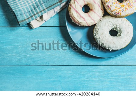 three glazed donuts on blue plate over blue wooden table top view