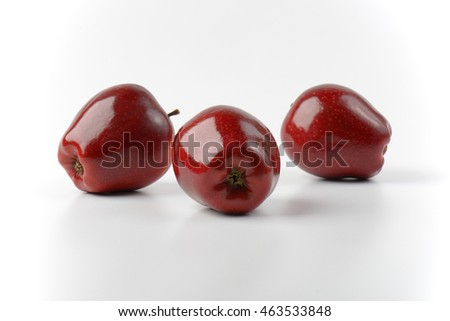 three glossy red apples on off-white background