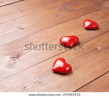 Three glossy red hearts over the brown wooden board surface as a love themed background composition