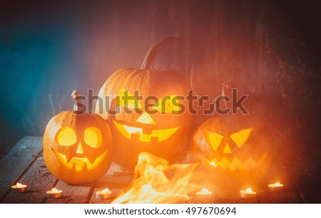 Three glowing halloween pumpkins symbolizing the head of old Jack, with smoke on wooden background. Soft focus. Shallow DOF
