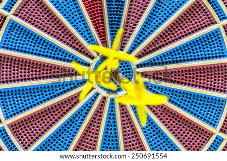 Three goals blurred in bulls eye of dartboard - stock photo