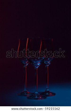 Three goblets on dark blue background with red glare