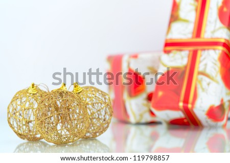 Three gold Christmas balls and gifts on white background