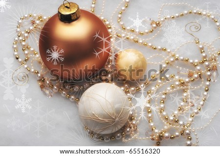 Three gold ornaments with beaded garland surrounding the trio