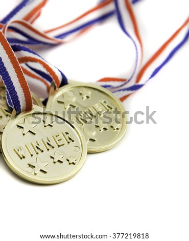 Three gold winner medals isolated against a white background. - stock photo