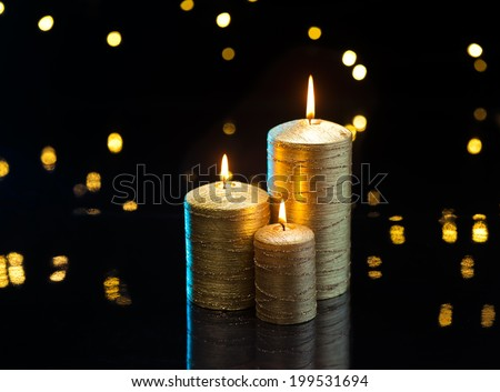 Three golden candles in front of dark background - stock photo