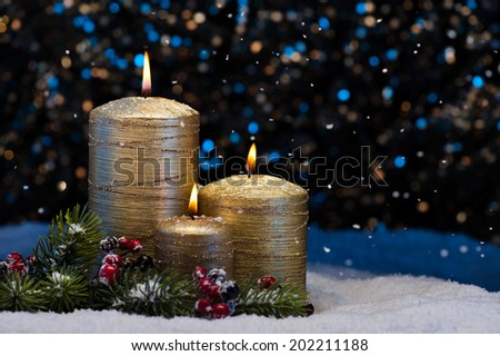 Three Golden Candles in snow with snowfall - stock photo