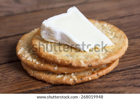 Three golden cheese crackers on wood. With cheese. - stock photo
