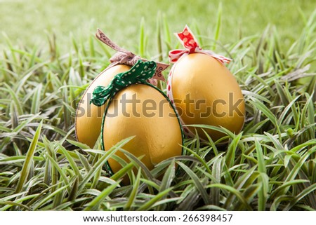 three golden easter eggs with colorful bow on green grass