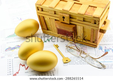 Three golden eggs and a golden key with a wooden chest on business and financial reports : Key success in sustainable growth investment concept - stock photo