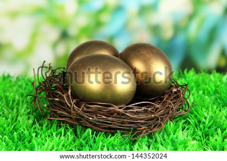 Three golden eggs in nest on grass on bright background - stock photo
