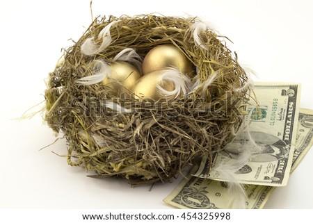 Three golden nest eggs on white background - stock photo