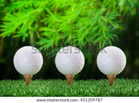 three Golf ball on tee pegs in nature green background