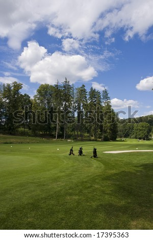 three golf trolleys standing on fairway of a beautiful golf course with dramatic summer sky - stock photo