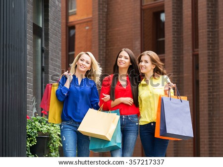 Three gorgeous female friends being happy with shopping bags in city center.