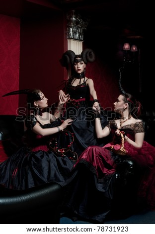 Three gothic girls with horns - stock photo