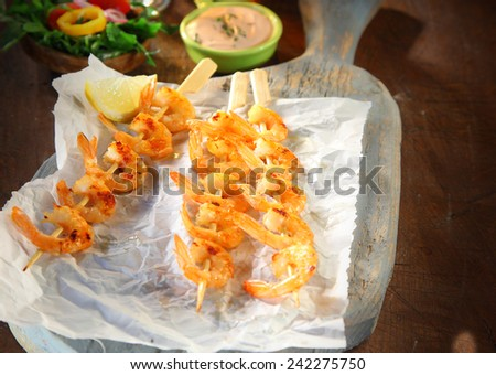 Three gourmet pink prawn or shrimp seafood kebabs grilled and flavored with with garlic served on crumpled white paper with lemon and a dipping sauce - stock photo
