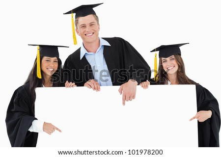 Three graduates pointing to the blank sign while smiling and looking at the camera - stock photo