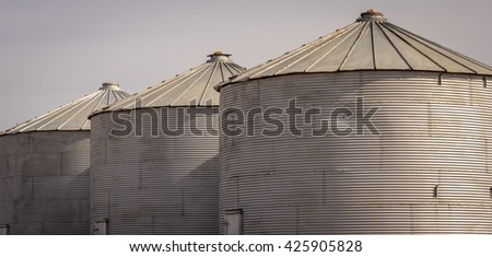 Three grain silos leading off into the distance - stock photo