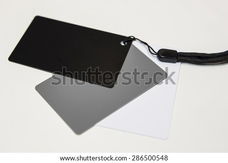 Three gray cards, darker and brighter, tied on a knob, on a white background.