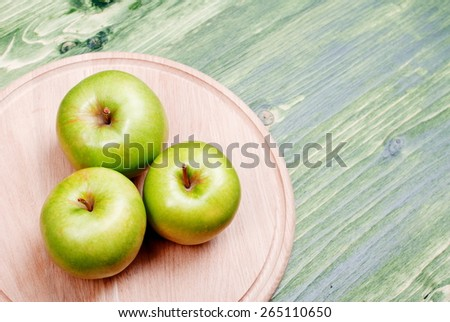 Three green apple on a cutting board in the bottom left corner  - stock photo