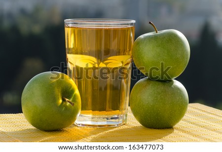 Three green apples and a large glass of apple juice are in the center of the shot outside in sunny weather