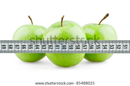 Three green apples behind meter on white background