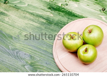 Three green apples in the bottom right corner of the table, top view - stock photo