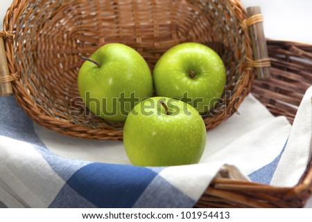 Three green apples in the brown wicker basket with a blue gingham cloth