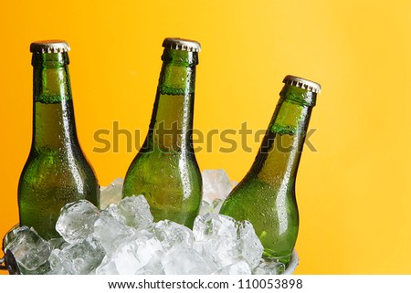 Three Green Beer Bottles in Ice Bucket with Condensation - stock photo