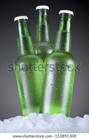 Three green beer bottles sitting on ice over a gray background. - stock photo