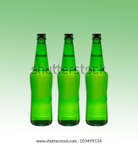 Three green beer bottles with caps on a green  background. Space for text - stock photo