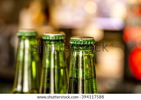 Three green bottles of beer in line sitting on bar with bar lights in background - stock photo