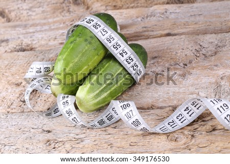 Three green fresh cucumber, wrapped with a white measuring tape on a brown wooden table, symbolizing a healthy diet, weight loss. - stock photo