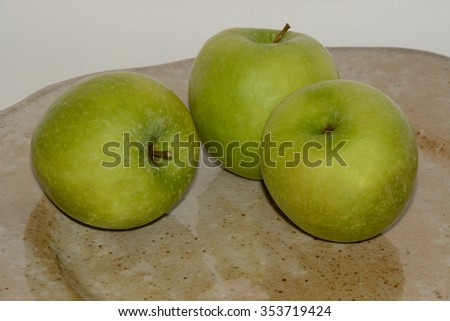 Three green Granny Smith Apples on handcrafted ceramic plate - stock photo