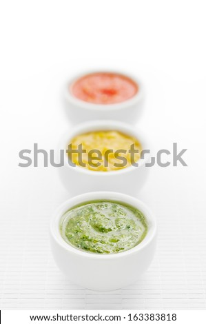 Three green, yellow and red sauces in a row - stock photo