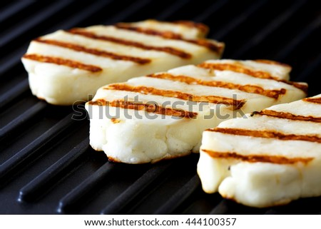 Three grilled slices of halloumi cheese on grill in perspective. With grill marks.