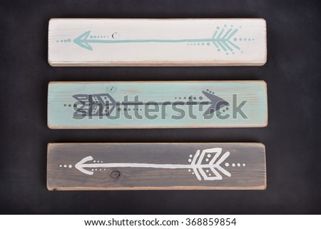 Three hand painted arrows on a wooden plank on a blackboard background - stock photo