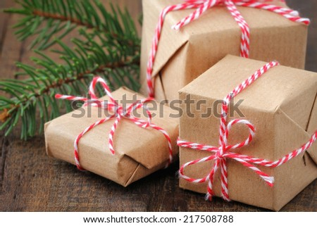 Three handcrafted Christmas gifts wrapped in brown paper and tied with a red and white festive twine - stock photo