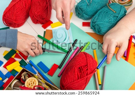 three hands and a lot of handicraft materials - stock photo