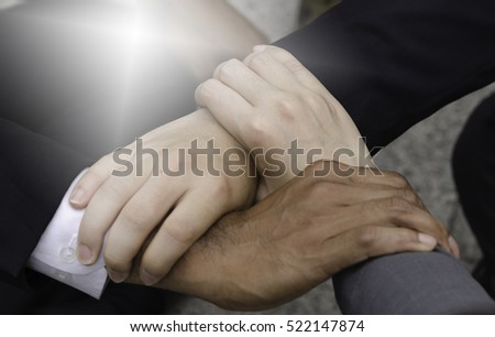 Three hands hold together ,business signs with white light.