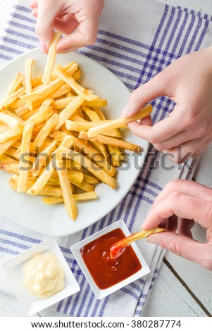 Three Hands Picking French Fries and Dipping in Ketchup and Mayonnaise