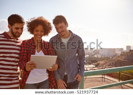 Three happily smiling young millennials looking at a tablet, the girl is holding while standing between the young men
