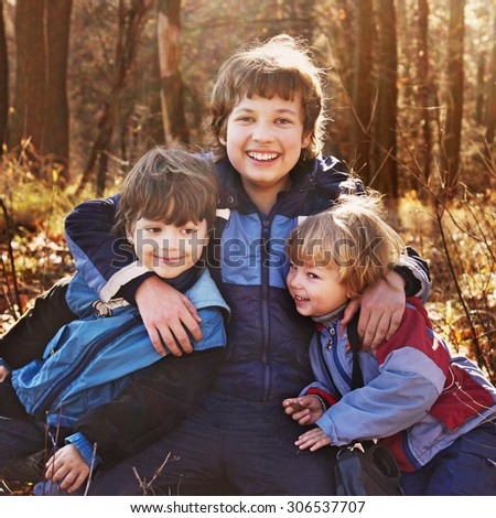three happy boys  in autumn forest
